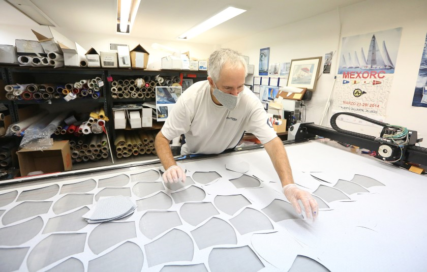 Ken Cooper removes the cutouts, which are the first process in making face coverings, on a vacuum table at the Ullman Sails Newport Beach workshop in Santa Ana on Wednesday.(Don Leach / Staff Photographer)